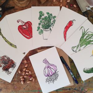 This is an image of a pack of 8 recycled cards, 'From the Plot' - reproductions of original lino prints by Becca Thorne